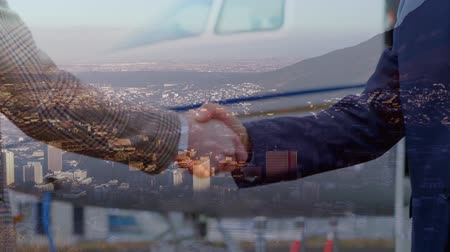 сочетание : Animation of businessmen shaking hands in agreement in front of a plane over cityscape with clouds on blue sky in the background. Global business in modern world concept combination image. Стоковые видеозаписи