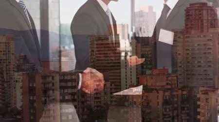 kombináció : Animation of businessmen shaking hands in agreement in slow motion over cityscape with clouds on blue sky in the background. Global business in modern world concept combination image.