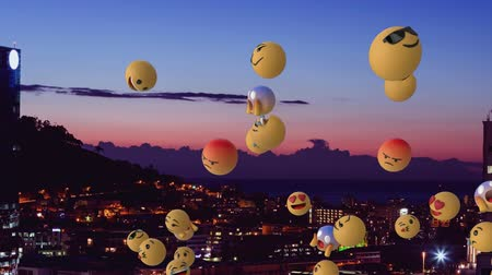 risonho : Animation of a group of multiple emoji icons flying from right to left over cityscape at sunset with clouds on blue sky in the background. Global social networking concept digital composite. Vídeos