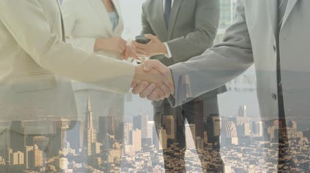 kombináció : Animation of Caucasian businessman and businesswoman shaking hands in agreement with their colleagues interacting in the background over cityscape with clouds on blue sky in the background. Global business in modern world concept combination image. Stock mozgókép