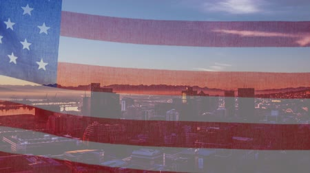 сочетание : Animation of waving American flag in front of a modern cityscape on a sunny day with clouds on blue sky in the background. Patriotism and modern city image combination concept. Стоковые видеозаписи