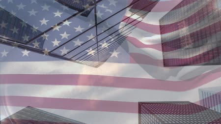組み合わせ : Animation of waving American flag in front of a modern cityscape on a sunny day with clouds on blue sky in the background. Patriotism and modern city image combination concept. 動画素材