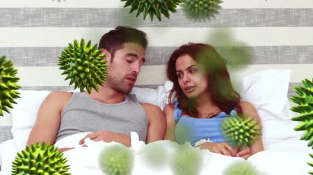 longontsteking : Animation of green macro corona virus spreading and floating with a sick Caucasian couple lying in bed, coughing and sneezing using tissues in the background. Global health warning scare spreading infections concept digital composite.