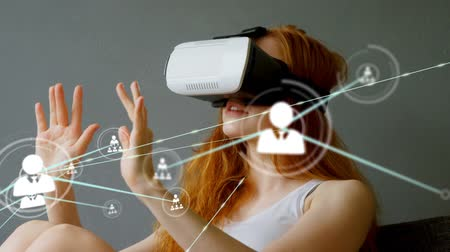 vr headset : Animation of network of connections with people icons with Caucasian woman wearing a Virtual Reality headset in the background. Global networking virtual reality and connections concept digital composite. Stock Footage