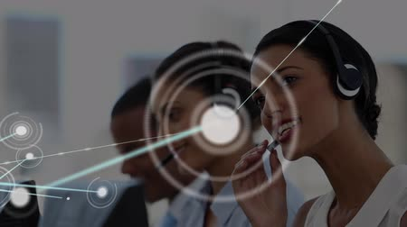 yardım hattı : Animation of network of connections with a group of office workers wearing phone headsets in a busy office in the background. Global networking and connections concept digital composite. Stok Video