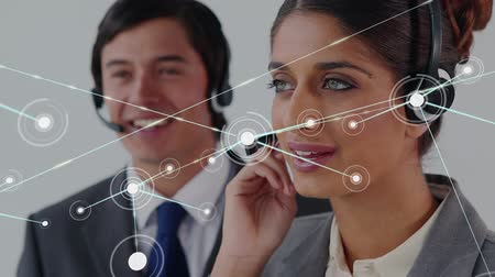 yardım hattı : Animation of network of connections with a mixed race businesswoman and Caucasian businessman wearing phone headsets in a busy office in the background. Global networking and connections concept digital composite.