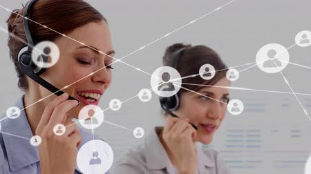 yardım hattı : Animation of network of connections with people icons with two female Caucasian office workers wearing phone headsets in a busy office in the background. Global networking and connections concept digital composite. Stok Video