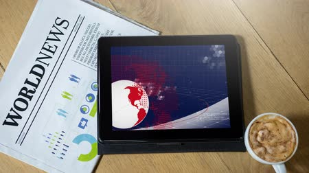 газета : Animation of the news screen with white and red globe spinning and global information processing displayed on digital tablet computer screen with World News newspaper and cup of coffee on wooden background. Global technology media and information network
