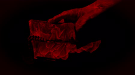 sekans : Animation of hands holding book with rosary beads filled with red light, flames and moving liquid reflected in surface in slow motion on black background. Multilayered film sequence concept digitally generated.