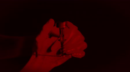 broca : Animation of female hands clasped together in praying gesture filled with red light, with close up of electric drill working in slow motion on black background. Multilayered film sequence concept digitally generated.