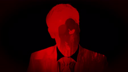 megtöltött : Animation of front view of a man filled with red light and silhouettes of kissing couple in slow motion on black background.  Multilayered film sequence concept digitally generated.