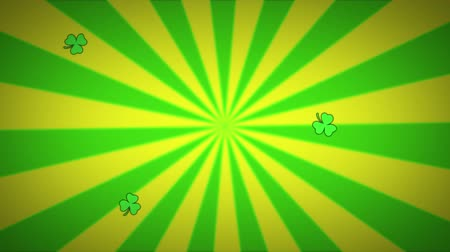 patron : Animation of St Patricks Day multiple floating green shamrocks falling yellow and green radiating stripes spinning in seamless loop in the background. Celebration of Irish culture concept digitally generated image. Stock Footage
