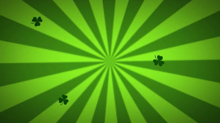 patron : Animation of St Patricks Day multiple floating green shamrocks falling light and dark green radiating stripes spinning in seamless loop in the background. Celebration of Irish culture concept digitally generated image.