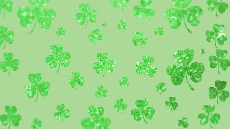 patron : Animation of St Patricks Day multiple shimmering green shamrocks falling in slow motion on light green background. Celebration of Irish culture concept digitally generated image.