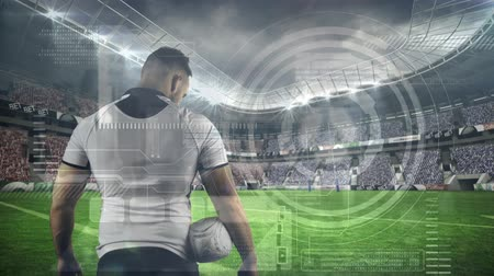 midiendo : Animation of data processing and statistics recording with rear view of male rugby player concentrating before a rugby match at a sports stadium in the background. Global sport and technology statistics data processing concept digital composite.