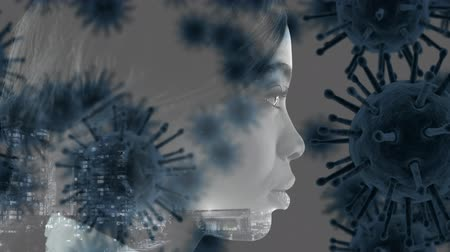 longontsteking : Animation of multiple grey macro corona virus spreading and floating with profile of a mixed race woman looking ahead on a grey background. Global health warning scare spreading infections concept digital composite. Stockvideo