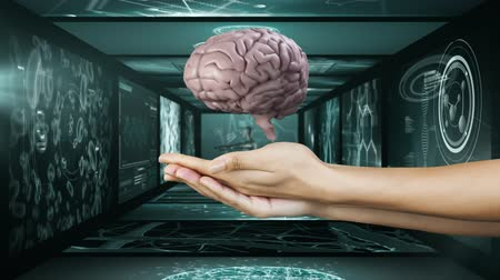 rezonans magnetyczny : Animation of 3d pink human brain rotating above hands of a woman in front of magnetic resonance imaging scan screens and DNA strand spinning in the background. Global medicine science and research network digitally generated image.