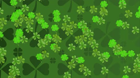 st patrick : Animation of St Patricks Day pattern of multiple rows of green shamrocks with a group of multiple moving green clover leaves on dark green background. Celebration of Irish culture concept digitally generated image.