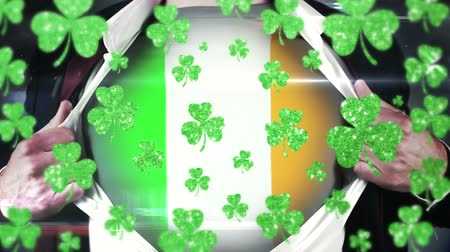 patron : Animation of St Patricks Day multiple shimmering floating green shamrocks with a man opening his shirt showing an Irish flag on in the background. Celebration of Irish culture concept digitally generated image. Stock Footage