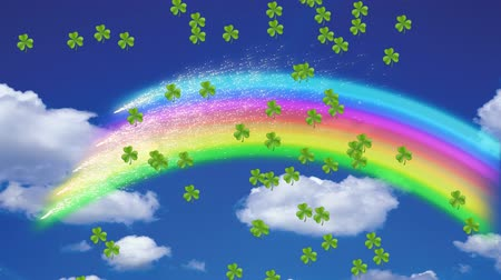 patron : Animation of St Patricks Day multiple shimmering floating green shamrocks with rainbow on blue sky with clouds in the background. Celebration of Irish culture concept digitally generated image. Stock Footage