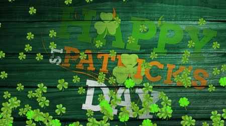 st patrick : Animation of the words Happy St. Patricks Day written in green, orange and white letters on green wooden boards, with multiple green shamrock clover leaves moving on green background. Celebration of Irish culture concept digitally generated image.