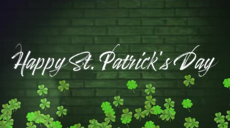 написанный : Animation of the words Happy St. Patricks Day written in white letters, with multiple green shamrock clover leaves moving on green brick wall background. Celebration of Irish culture concept digitally generated image.