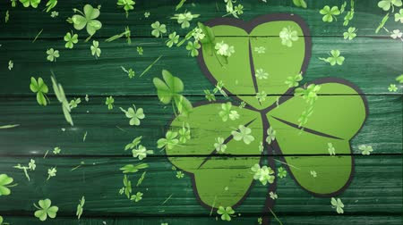 patron : Animation of St Patricks Day multiple shimmering falling light green shamrocks with green clover leaf on dark green wooden boards in the background. Celebration of Irish culture concept digitally generated image.