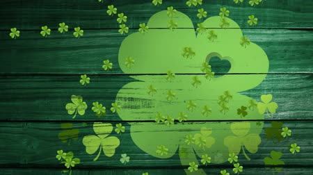 patron : Animation of St Patricks Day multiple falling light green shamrocks with green clover leaf on dark green wooden boards in the background. Celebration of Irish culture concept digitally generated image.