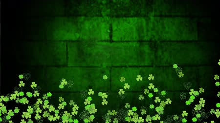 patron : Animation of St Patricks Day multiple shimmering moving green shamrocks with spot of light on glowing green brick wall background. Celebration of Irish culture concept digitally generated image.