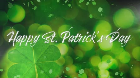 patron : Animation of the words Happy St. Patricks Day written in white letters, with multiple green shamrock clover leaves moving on green background. Celebration of Irish culture concept digitally generated image.