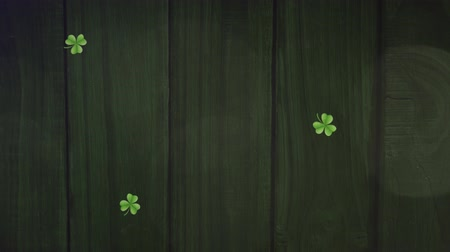 patron : Animation of St Patricks Day multiple shimmering falling light green shamrocks with spots of light on dark green wooden boards in the background. Celebration of Irish culture concept digitally generated image.