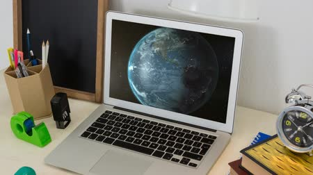 データベース : Animation of globe spinning displayed on screen of laptop computer on desk with alarm clock and office items. Global communication modern technology concept digitally generated image.