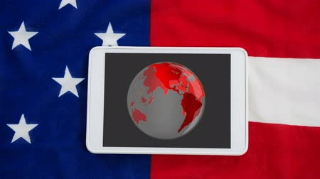 データベース : Animation of globe spinning displayed on screen of digital tablet on grey background with American flag. Global communication modern technology concept digitally generated image.