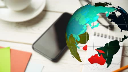 world cup : Animation of multi coloured transparent globe spinning in front of smartphone, cup of coffee and papers on white wooden desk in the background. Global communication modern technology concept digitally generated image.