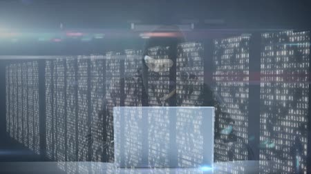 gondoskodó : Animation of man in a mask hacking laptop computer, data processing and digital information flowing through network of computer servers in a server room with white light trails flowing on surface. Global network of internet service provider or data proces