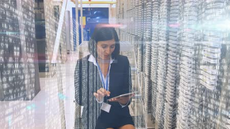 データベース : Animation of mixed race woman using a tablet computer, data processing and digital information flowing through network of computer servers in a server room with white light trails flowing on surface.