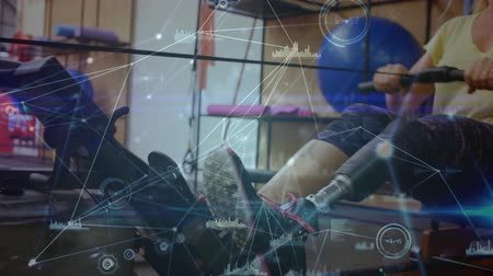 kürek çekme : Animation of data processing and statistics recording with Caucasian female disabled athlete with prosthetic leg exercising in a gym on a rowing machine in the background. Global sport disability and technology statistics data processing concept digital c Stok Video