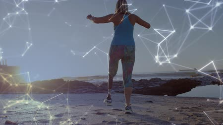emelt : Animation of data processing and statistics recording with disabled woman with prosthetic leg walking exercising and raising her arms by the sea in the background. Global sport disability and technology statistics data processing concept digital composite