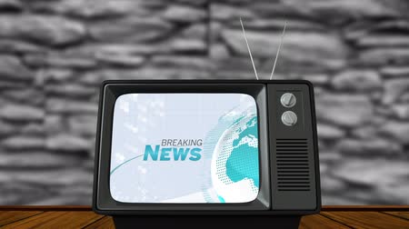 írott : Animation of the words Breaking News written in grey and blue over spinning globe of a new programme displayed on a vintage television set with grey wall in the background. Global information news concept digitally generated image.