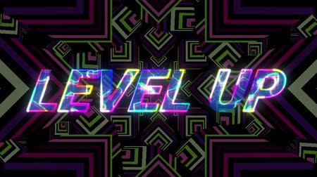 написанный : Animation of the words Level Up written in multicoloured changing shimmering letters written over kaleidoscope of stars moving in hypnotic motion in the background. Video computer game screen and digital interface concept digitally generated image.