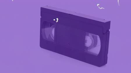 změna : Animation of distressed vintage film showing spinning video cassette on purple background. Vintage entertainment and movement concept digitally generated image.