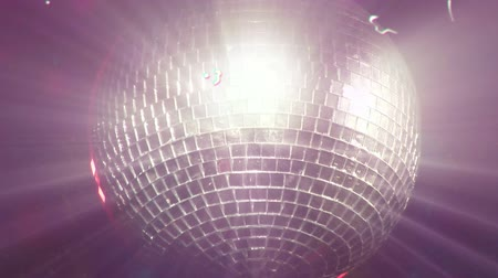 světlo : Animation of distressed vintage film showing glowing disco mirror ball spinning with splashes of colour in the background. Vintage entertainment and movement concept digitally generated image.