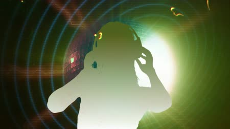 světlo : Animation of distressed vintage film showing white silhouette of a dj with headphones on dancing at a music concert with disco mirror ball rotating over green and yellow glowing background. Vintage entertainment colour and movement concept digitally gener