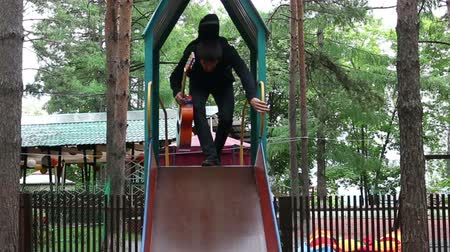 pursuit plane : The guy with a guitar on a Hill, Playground, Counts and Slides Down, a Small Childrens Slide Stock Footage