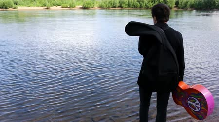 verse : Man walks edge of river with acoustic guitar seeking inspiration for songwriting, music. hippie.