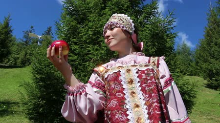 созерцать : Girl in Russian folk costume contemplate red apple Стоковые видеозаписи