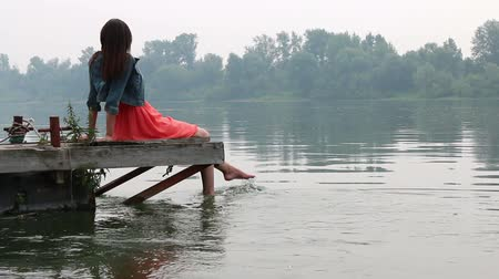 platform edge : Womans legs hanging into the river on wooden pier