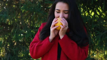 cheirando : Girl in red coat is holding an orange