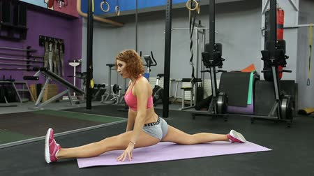 vöröshajú : Redhead woman stretching leg on mat in gym