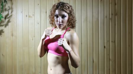 puncs : Pretty girl stand in pose of boxer in the gym